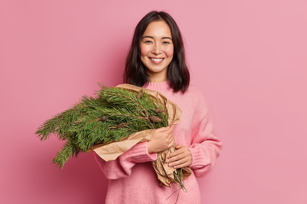 Pleased optimistic dark haired woman holds evergreen fir tree branches arranged in bouquet smiles gladfully has toothy smile wears sweater poses