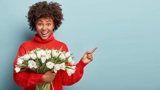 La signora ottimista e soddisfatta ha un taglio di capelli ricci, indica con l'indice, indossa un maglione invernale rosso, tiene in mano tulipani bianchi e mostra uno spazio vuoto per i tuoi contenuti pubblicitari. guarda qui! fiori, donne
