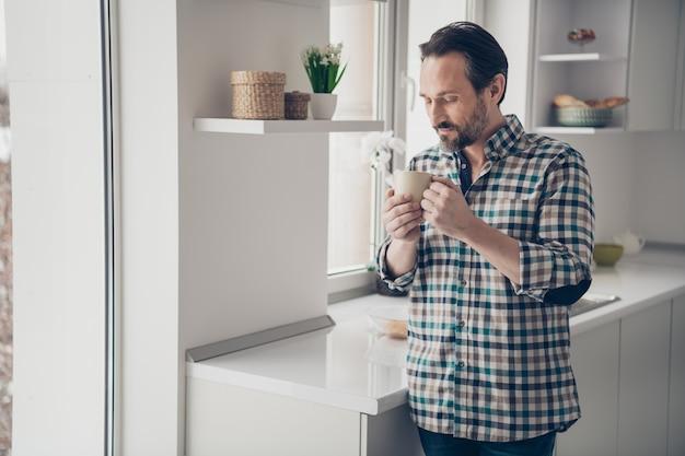 큰 창 근처에 서있는 손에 맛있는 커피 잔을 들고 좋은 분위기의 남자에 잘 생긴 좋은 기쁜 낙관적 휴식을 기쁘게