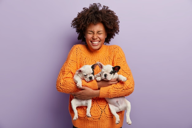 Pleased overjoyed dark skinned female with afro haircut, holds two little dogs, closes eyes, wears orange sweater, poses over purple wall. positive girl plays with favorite pets at home