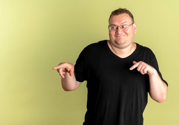 Soddisfatto uomo in sovrappeso con gli occhiali che indossa una maglietta nera con le dita indice sul lato in piedi sopra la parete chiara
