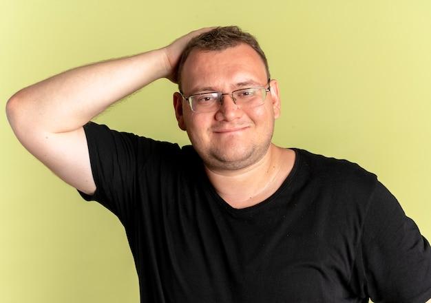가벼운 벽 위에 서있는 카메라를보고 검은 티셔츠를 입고 안경에 만족과 체중 남자