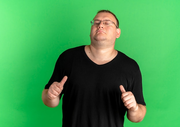 緑の壁の上に立っている自分を指している黒いtシャツを着て眼鏡をかけた太りすぎの男を喜ばせる