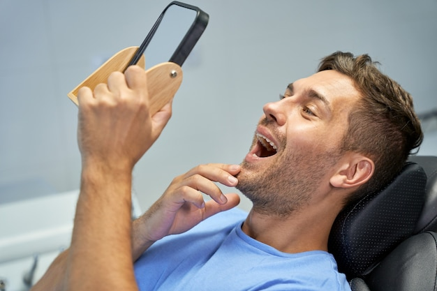 Pleased patient of dental clinic beholding his teeth in mirror