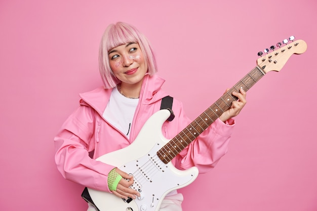 Pleased pensive female rock musician play white electric guitar perform popular song enjoys musical holiday wears pink jacket gloves stands indoor. famous artist has rehearsal before concert