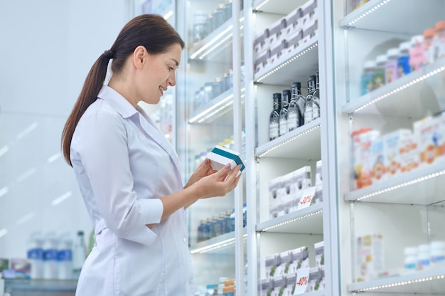 Pleased pharmaceutist standing before the drugstore display cabinet