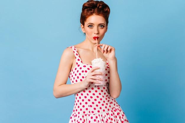 飲み物を飲み、カメラを見て喜んでピンナップ女性。ミルクセーキを楽しんでいる水玉模様のドレスを着た女の子の正面図。