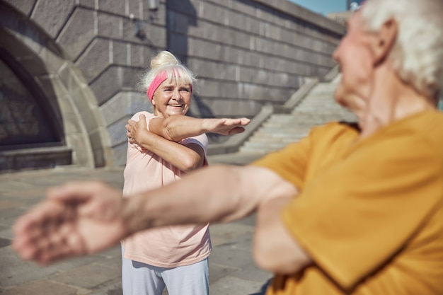 Pleased pleasant fit aged caucasian lady smiling at a gray-haired man during the outdoor workout