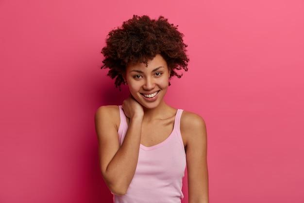 La donna afroamericana positiva e positiva guarda direttamente con un sorriso affascinante, tocca delicatamente il collo, si sente soddisfatta, ha i capelli ricci e folti, vestita in abbigliamento casual, isolato sul muro rosa