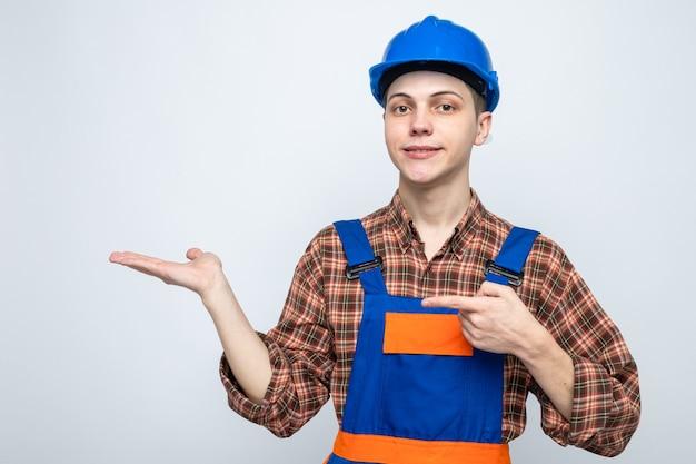 제복을 입은 젊은 남성 건축업자를 잡고 있는 척하고 무언가를 가리키는 것을 기쁘게 생각합니다