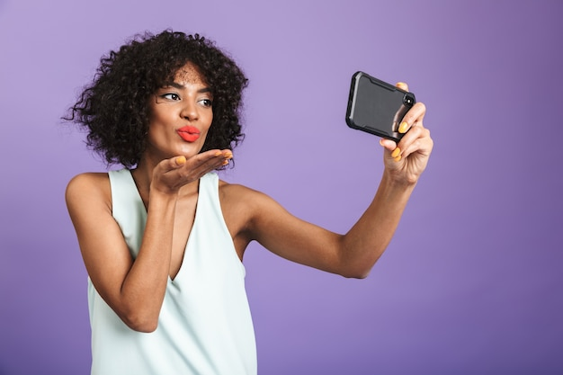 Pleased pretty african woman making selfie on smartphone and sending air kiss over violet background