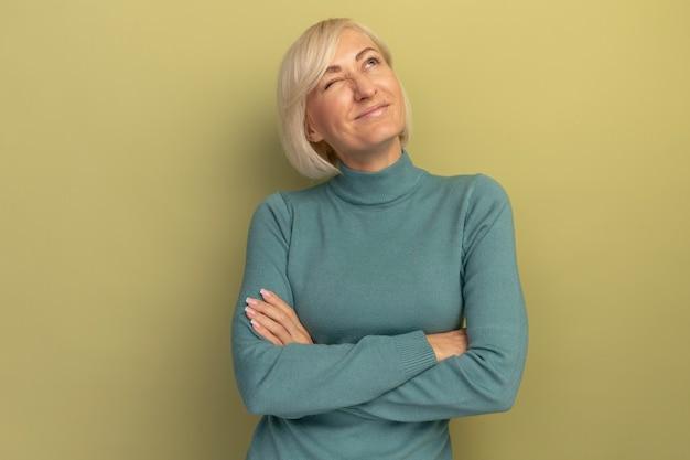 Pleased pretty blonde slavic woman blinks eye looking up on olive green