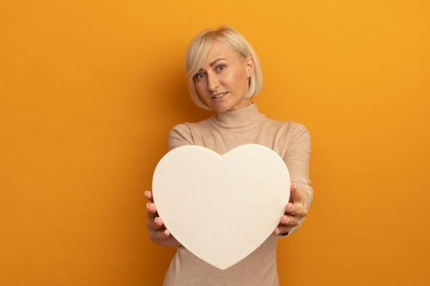 La donna slava abbastanza bionda soddisfatta tiene la forma del cuore sull'arancio