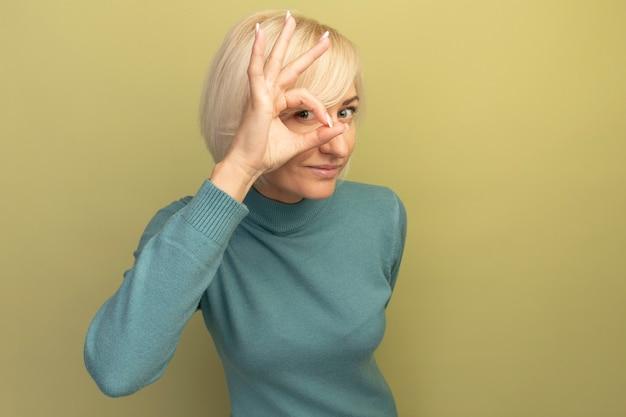 La donna slava bionda graziosa soddisfatta guarda davanti attraverso le dita isolate sulla parete verde oliva