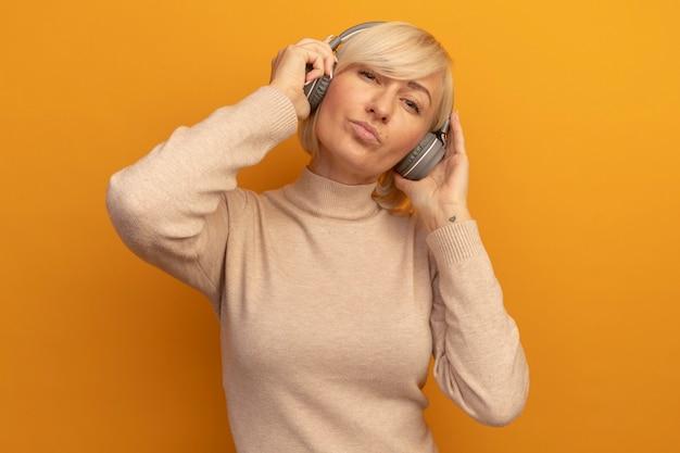 헤드폰에 만족 된 예쁜 금발의 슬라브 여자는 오렌지에 카메라를 본다