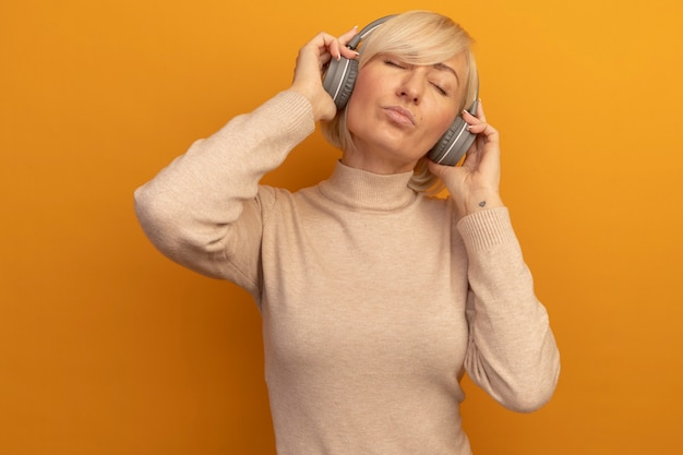헤드폰에 만족 된 예쁜 금발의 슬라브 여자는 오렌지에 닫힌 눈으로 서