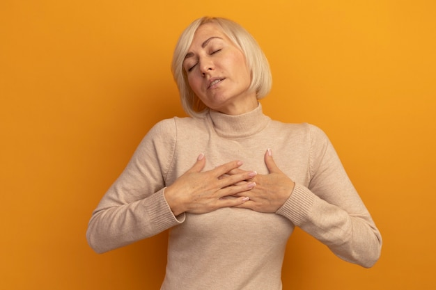 닫힌 눈을 가진 기쁘게 예쁜 금발의 슬라브 여자는 오렌지에 가슴에 손을 넣습니다.