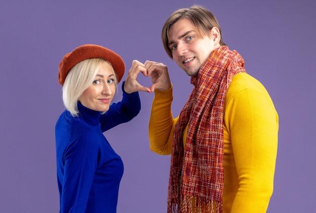 バレンタインデーに一緒にサインを身振りで示す彼の首の周りにスカーフを持ったベレー帽と笑顔のハンサムなスラブ人の幸せなきれいな金髪の女性