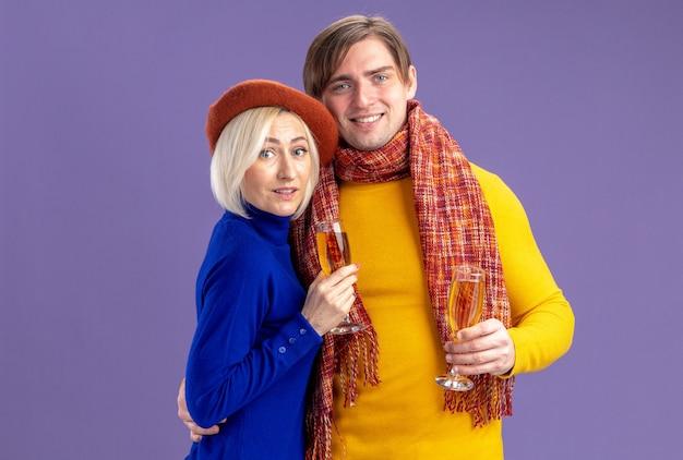 Piacevole bella donna bionda con berretto e bell'uomo slavo con sciarpa intorno al collo tenere bicchieri di champagne