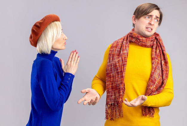 ベレー帽を持って手をつないで、コピースペースのある白い壁に隔離された首にスカーフを持った不愉快なハンサムなスラブ人を見て満足しているきれいなブロンドの女性
