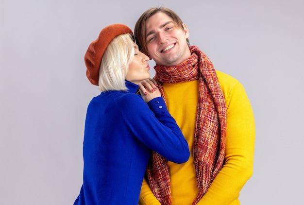 발렌타인 데이에 목에 스카프를 두르고 웃고 있는 잘생긴 슬라브 남자에게 키스하는 척 베레모를 한 예쁜 금발 여성을 기쁘게 생각합니다.