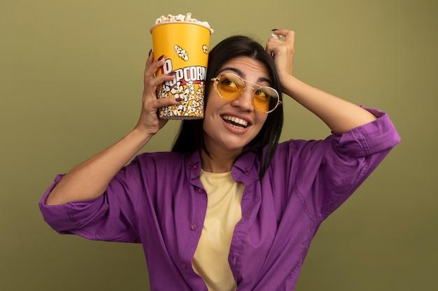 La ragazza caucasica abbastanza mora soddisfatta in occhiali da sole tiene il secchio di popcorn e mette la mano sulla testa che osserva in su sul verde oliva
