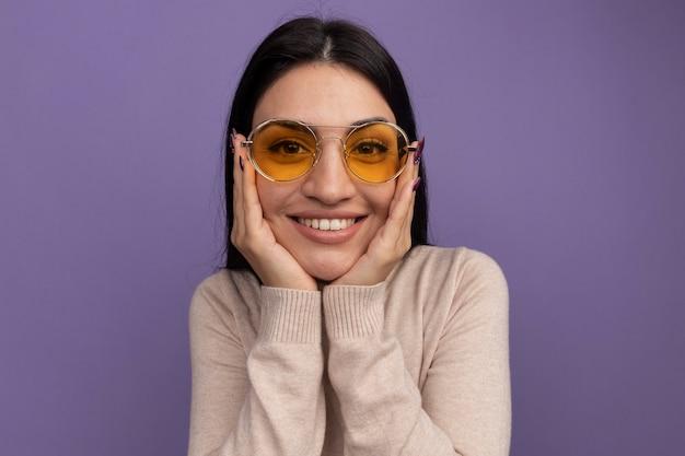 La ragazza caucasica abbastanza mora soddisfatta in occhiali da sole mette le mani sul mento sulla viola