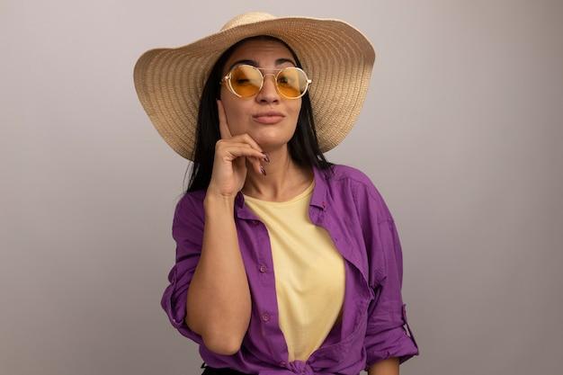 Soddisfatta bella donna mora in occhiali da sole con cappello da spiaggia lampeggia gli occhi e mette il dito sul viso isolato sul muro bianco