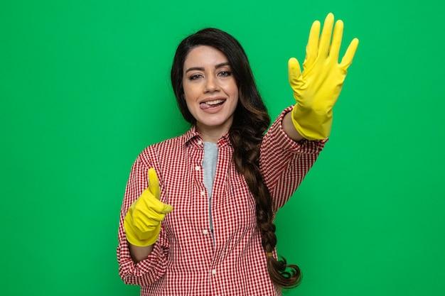 Piacevole donna delle pulizie piuttosto caucasica con guanti di gomma che allunga la mano e fa il pollice in alto