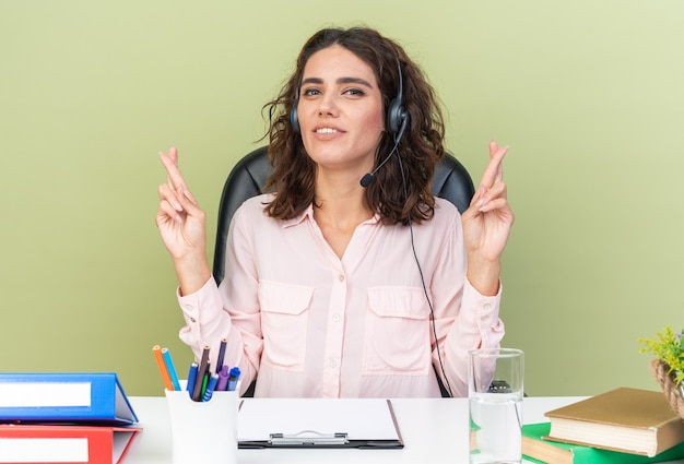 Pleased pretty caucasian female call center operator on headphones sitting at desk with office tools crossing her fingers