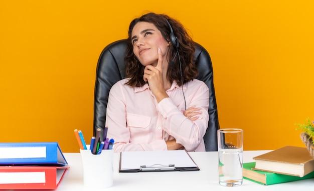 Piacevole operatore di call center femminile caucasica sulle cuffie seduto alla scrivania con strumenti da ufficio mettendo il dito sul mento e guardando in alto