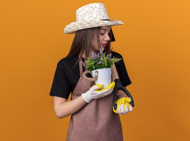 植木鉢を保持し、スペードを見てガーデニングの帽子と手袋を身に着けているかなり白人女性の庭師を喜ばせます