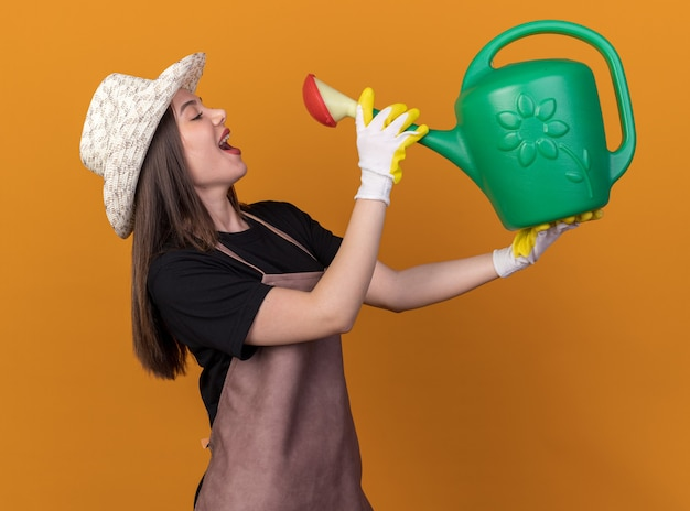 オレンジ色のじょうろから飲むふりをしてガーデニングの帽子と手袋を身に着けているかなり白人女性の庭師を喜ばせる