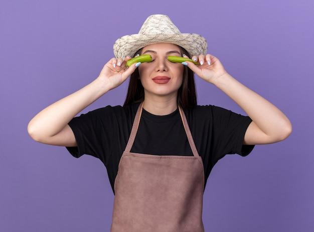 コピースペースで紫色の壁に分離された壊れた唐辛子の部分で目を覆うガーデニングの帽子をかぶっているかなり白人女性の庭師を喜ばせます