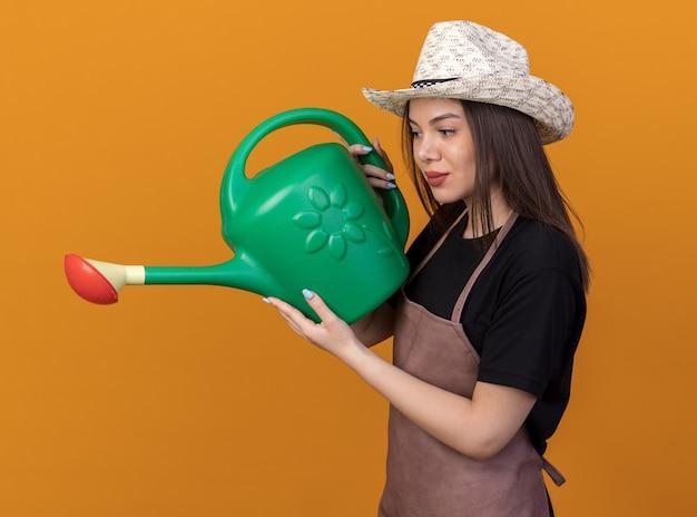 じょうろを持って見ているガーデニング帽子をかぶっているかなり白人女性の庭師を喜ばせます