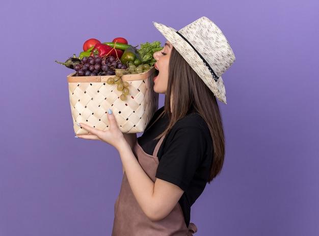 野菜のバスケットを持って噛むふりをしてガーデニング帽子をかぶっているかなり白人の女性の庭師を喜ばせます