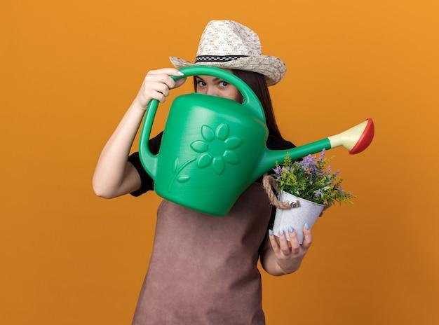 Piacevole giardiniere femmina caucasica che indossa cappello da giardinaggio tenendo un vaso di fiori e attraverso un annaffiatoio isolato sulla parete arancione con spazio di copia
