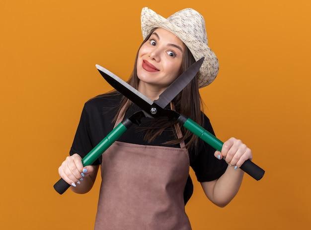 コピースペースとオレンジ色の壁に分離されたガーデニングはさみを保持しているガーデニング帽子をかぶっているかなり白人女性の庭師を喜ばせる