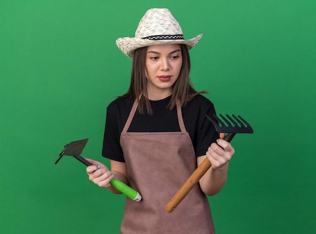 Piacevole giardiniere femmina caucasica che indossa cappello da giardinaggio tenendo il rastrello zappa e guardando il rastrello