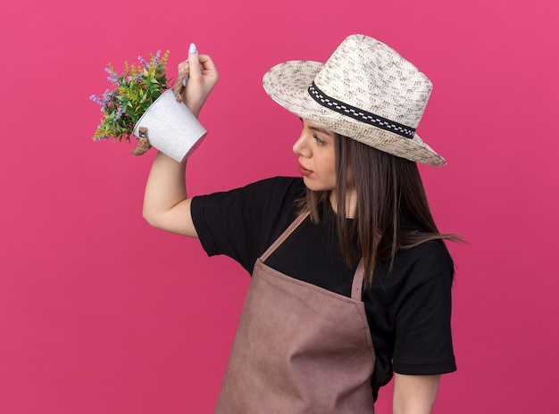 Piacevole giardiniere femmina caucasica che indossa cappello da giardinaggio tenendo e guardando i fiori in vaso