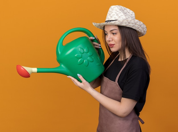 Pleased pretty caucasian female gardener wearing gardening hat holding and looking at watering can