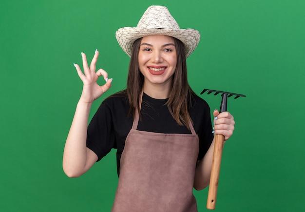 熊手を保持し、コピースペースで緑の壁に分離されたokサインを身振りで示すガーデニング帽子を身に着けているかなり白人女性の庭師を喜ばせる