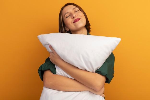 Довольная красивая кавказская женщина держит подушку на оранжевом