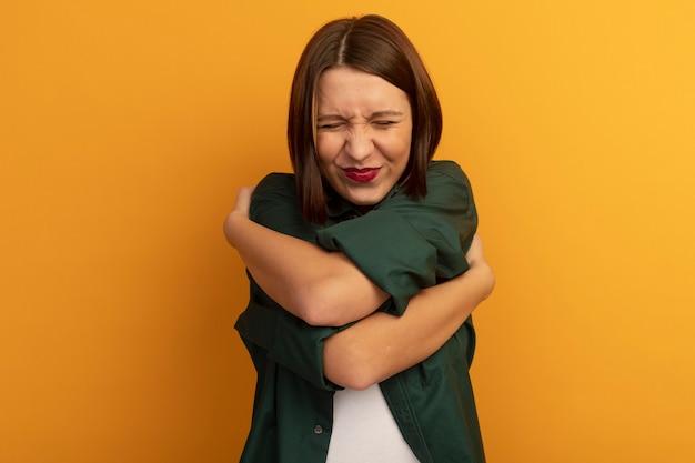 満足しているかなり白人の女性はオレンジ色の腕を組んで自分自身を抱きしめます