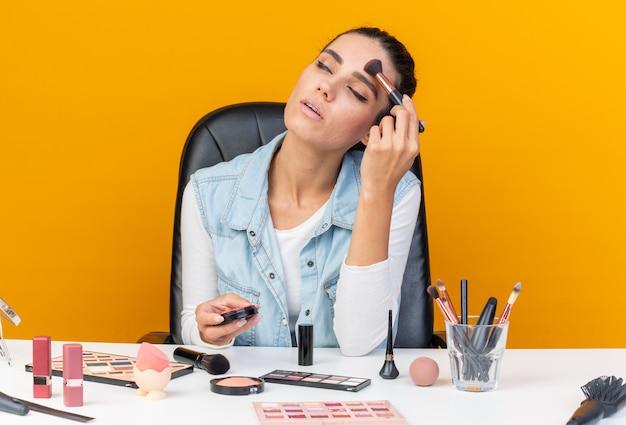 コピースペースとオレンジ色の壁に分離された化粧ブラシで赤面を保持し、適用する化粧ツールでテーブルに座っているかなり白人女性を喜ばせます