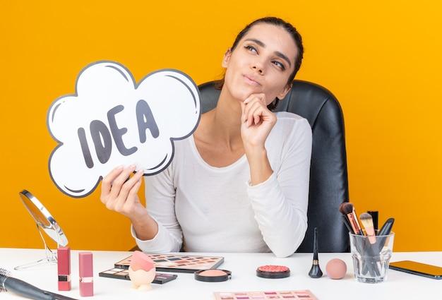 행복한 백인 여성이 화장 도구를 들고 테이블에 앉아 턱에 손을 대고 복사 공간이 있는 주황색 벽에 격리된 면을 바라보는 아이디어 거품을 들고 있습니다.