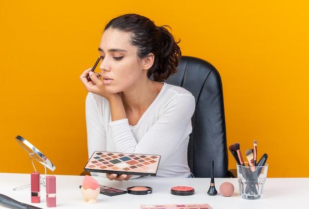 Donna abbastanza caucasica contenta che si siede al tavolo con strumenti per il trucco che tiene la tavolozza dell'ombretto e applica l'ombretto con il pennello per il trucco isolato sulla parete arancione con lo spazio della copia