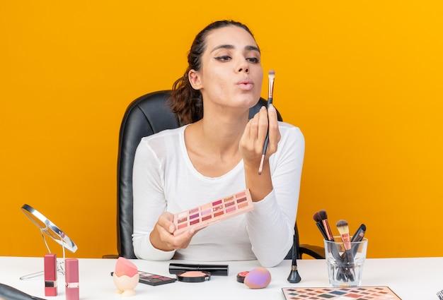 Piacevole donna caucasica seduta al tavolo con strumenti per il trucco che tiene la tavolozza dell'ombretto e guarda i pennelli per il trucco isolati sulla parete arancione con spazio per le copie