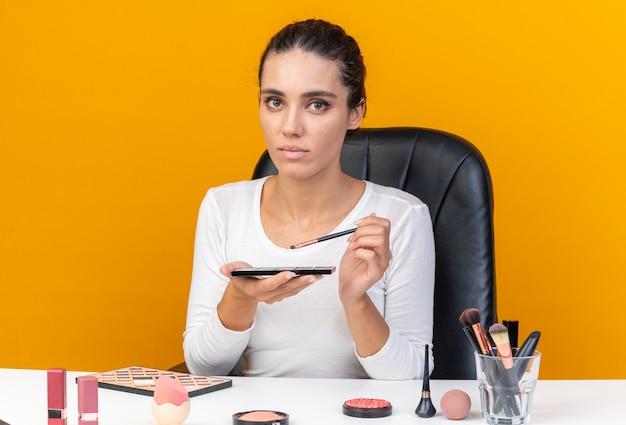 Piacevole donna caucasica seduta al tavolo con strumenti per il trucco che tiene la tavolozza dell'ombretto e il pennello per il trucco isolato sulla parete arancione con spazio per le copie