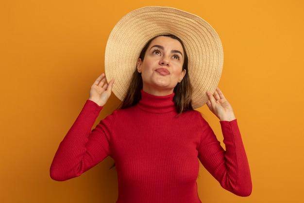 ビーチ帽子をかぶった幸せなかなり白人女性はオレンジ色を見上げます